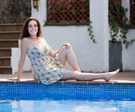 Girl in dress resting near pool Royalty Free Stock Photo
