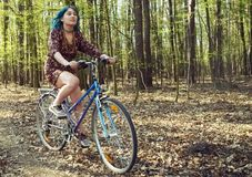 The girl in the dress rides a bicycle through the forest. stock photography