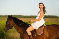 Girl in dress riding on a brown horse Stock Photo