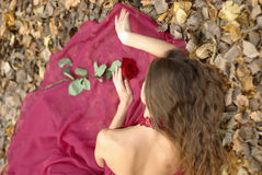 Girl in dress with rose lying Stock Photos