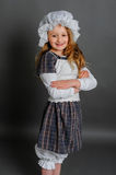 Girl in dress rustic vintage on a gray background. Crossed her arms and a smile Royalty Free Stock Photo