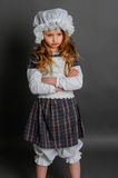 Girl in dress rustic vintage on a gray background. Crossed her arms and upset Stock Photos