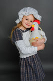 Girl in dress rustic vintage holds a chicken in a basket. Stock Photos