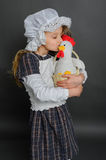 Girl in dress rustic vintage holds a chicken and kisses. With his eyes closed Royalty Free Stock Photos
