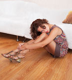 Girl in a dress and sandals, sitting on the floor Royalty Free Stock Photography