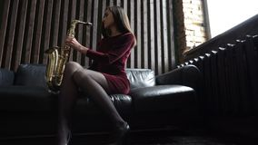 Girl in dress with saxophone on black leather couch in retro room near window stock video footage