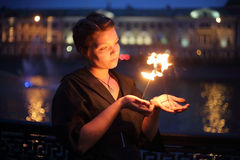 A girl in dress shows a fire show. Stock Image
