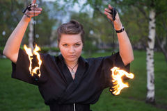 A girl in dress shows a fire show. stock photography