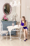 Girl dress sits at table in cosy cafe. Royalty Free Stock Images