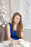 Girl dress sits at table in cosy cafe. Stock Photo