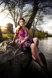 Girl in dress sitting on cliff on riverbank Stock Images