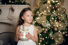 Girl in dress sitting near christmas tree and holding gifts Royalty Free Stock Photos
