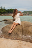 Girl in dress sitting on a rock by the sea Stock Photography