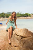 Girl in dress sitting on a rock by the sea Royalty Free Stock Image