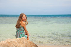 Girl in dress sitting on a rock by the sea Royalty Free Stock Photo