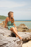 Girl in dress sitting on a rock by the sea Royalty Free Stock Photos