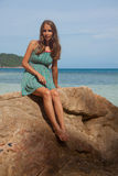 Girl in dress sitting on a rock by the sea Stock Photos