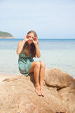 Girl in dress sitting on a rock by the sea Stock Images