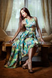 Girl in dress sitting in a room. Stock Photography