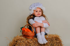 Girl in dress sitting on a rustic vintage hay. With basket of carrots Royalty Free Stock Photo