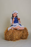 Girl in dress sitting on a rustic vintage straw bale. Girl in dress sitting on a rustic vintage straw bale Royalty Free Stock Photography