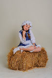 Girl in dress sitting on a rustic vintage straw bale. Royalty Free Stock Photo