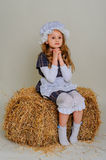 Girl in dress sitting on a rustic vintage straw bale. Girl in dress sitting on a rustic vintage straw bale Stock Images