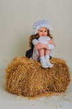 Girl in dress sitting on a rustic vintage straw bale. Royalty Free Stock Photos