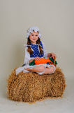 Girl in dress sitting on a rustic vintage straw bale Stock Image
