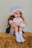 Girl in dress sitting on a rustic vintage straw bale. Stock Images