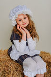 Girl in dress sitting on a rustic vintage straw bale. Royalty Free Stock Photography