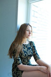 Girl in dress sitting by the window Royalty Free Stock Image