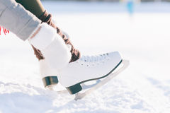 Girl in dress skates mittens tying shoelaces Stock Images