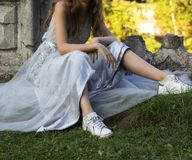 Girl in a dress and sneakers sits on the grass stock photos