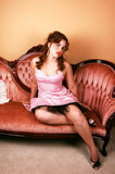 Girl in dress on sofa. Royalty Free Stock Image
