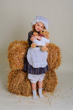 Girl in dress standing near a rustic vintage hay with a toy. Royalty Free Stock Photo