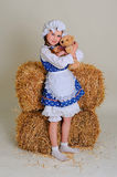 Girl in dress standing near a rustic vintage hay with a toy. Royalty Free Stock Photography