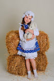 Girl in dress standing near a rustic vintage hay with a toy. Stock Photos