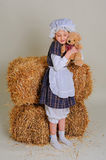 Girl in dress standing near a rustic vintage hay with a toy. Stock Photography