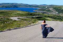 The girl in the dress is standing on the road. Girl in the dress is standing on the road going beyond the horizon Stock Photography