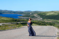Girl in the dress is standing on the road. Going beyond the horizon Royalty Free Stock Photos