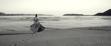 A girl in a dress is standing by the sea. Girl in a dress standing by the sea and looking out into the distance Royalty Free Stock Photography