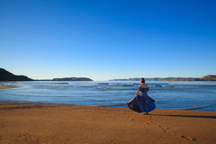 A girl in a dress is standing by the sea. Girl in a dress standing by the sea and looking out into the distance Royalty Free Stock Images
