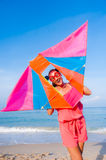 Girl in dress with sunglasses on the sea beach. Sunrise beach side, Girl playing with kite and have a joy, smile royalty free stock image