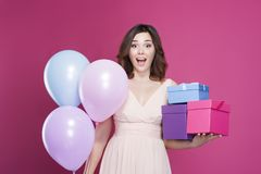 Girl in a dress, is surprised and holds gifts in hand, on a pink background stock photography