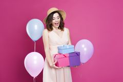 Girl in a dress, surprised and holds gifts in her hands, on a pink background royalty free stock photo