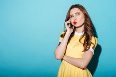 Girl in dress talking on mobile phone and looking away Royalty Free Stock Images