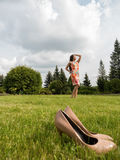 The girl in the dress took off her shoes and was enjoying herself. The girl walks barefoot on the grass. Beige shoes in the foregr stock photo