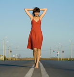 Girl in dress walk barefoot on empty road Royalty Free Stock Photography