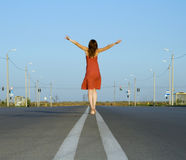 Girl in dress walk barefoot on empty road stock photo